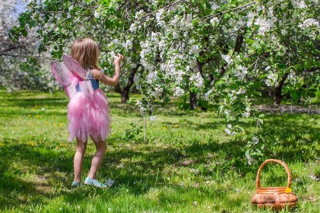 Bambina adorabile con il canestro della paglia nel meleto sbocciante