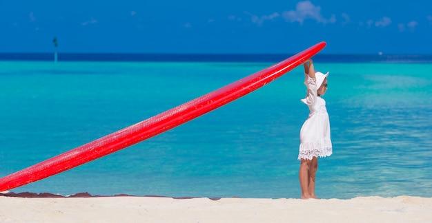 Bambina adorabile con il grande surf rosso durante la vacanza tropicale