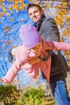 Bambina adorabile con il padre felice divertendosi nel parco di autunno un giorno soleggiato