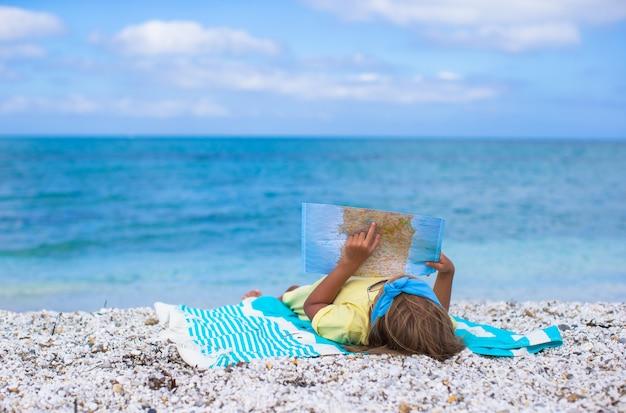 Bambina adorabile con la grande mappa sulla vacanza tropicale della spiaggia