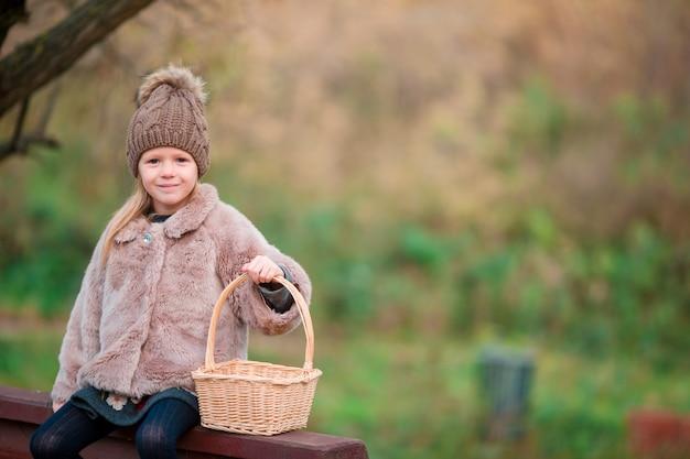 Bambina adorabile con un canestro nel parco di autunno all'aperto