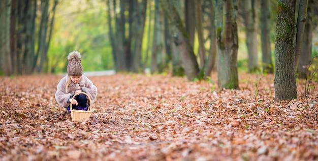 Bambina adorabile con un cestino nel giorno di autunno all'aperto in bella foresta