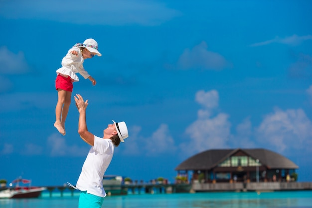 Bambina adorabile e padre felice durante la vacanza tropicale della spiaggia