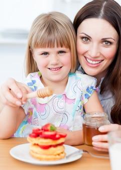 Bambina adorabile e sua madre che mettono miele sulle cialde