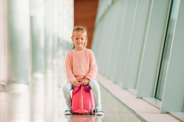 Bambina adorabile in aeroporto con l'imbarco aspettante dei suoi bagagli