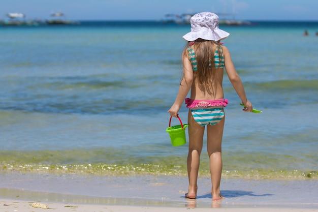 Bambina adorabile in bello costume da bagno che cammina al tropicale