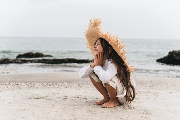 Bambina adorabile in cappello di paglia in spiaggia durante le vacanze estive