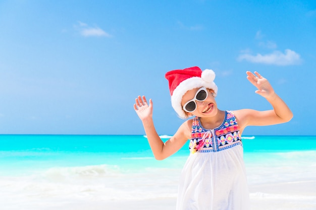 Bambina adorabile in cappello di santa durante la vacanza della spiaggia di natale. bambino alle vacanze al mare di natale