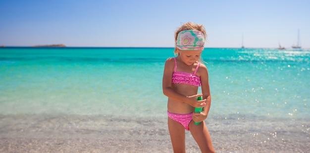 Bambina adorabile in costume da bagno con la bottiglia di lozione solare