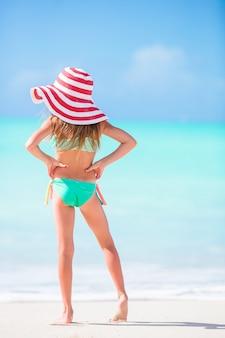 Bambina adorabile in grande cappello rosso che cammina lungo la spiaggia caraibica della sabbia bianca