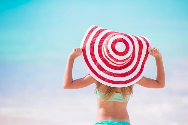 Bambina adorabile in grande cappello rosso sulla spiaggia caraibica