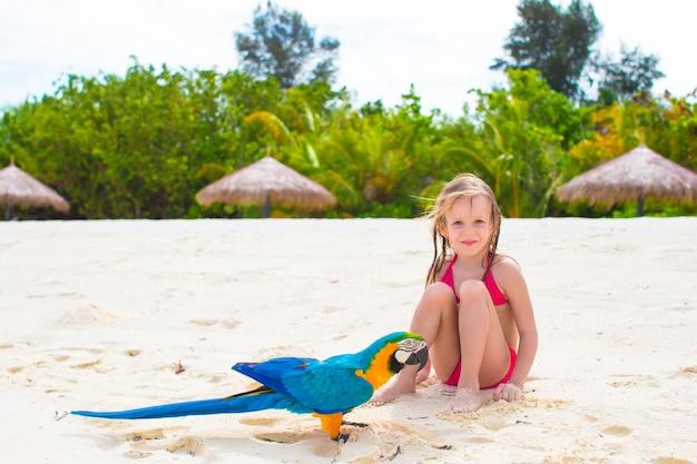 Bambina adorabile in spiaggia con pappagallo colorato