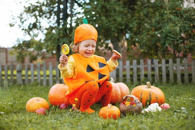Bambina adorabile in vestiti a tema di halloween che si siede su una grande zucca arancione
