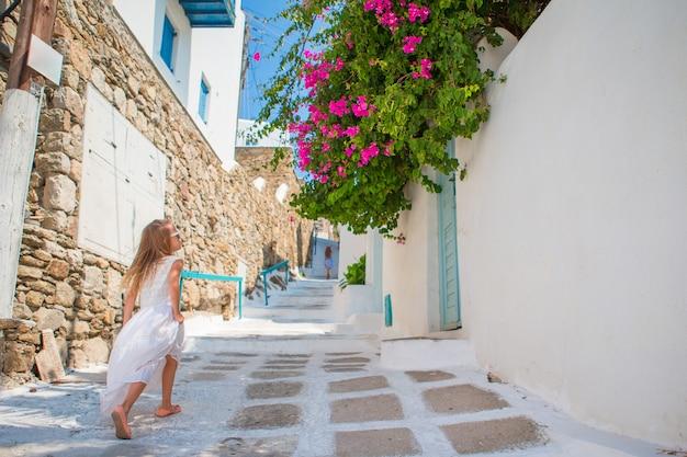 Bambina adorabile in vestito bianco divertendosi all'aperto. scherzi alla via del villaggio tradizionale greco tipico con le pareti bianche e le porte variopinte sull'isola di mykonos, in grecia