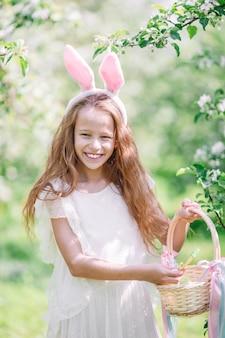 Bambina adorabile nel giardino delle mele di fioritura il bello giorno di molla