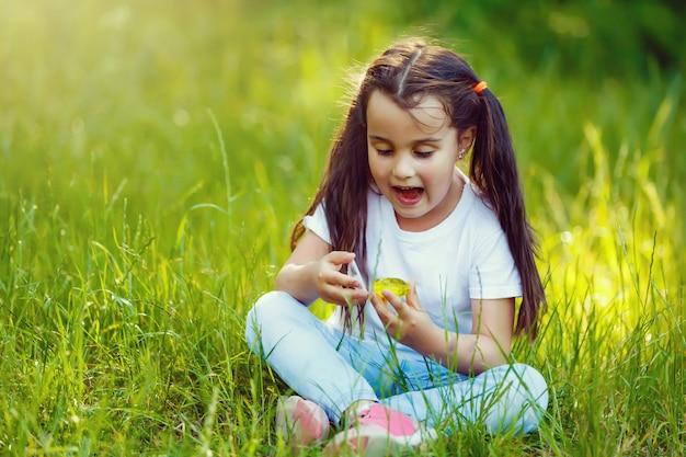 Bambina adorabile sorpresa che si siede nell'erba
