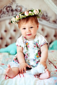 Bambina affascinante in corona di rose si siede sulle coperte morbide