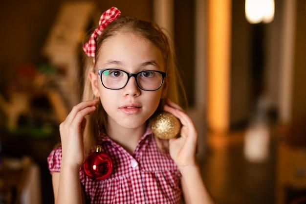 Bambina affascinante in vestiti bianchi e rossi con la decorazione di natale