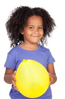 Bambina africana adorabile con l'aerostato giallo isolato sopra bianco