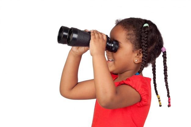 Bambina africana guardando attraverso il binocolo