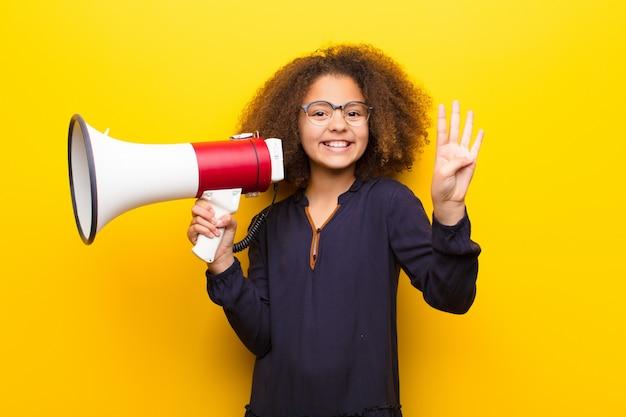 Bambina afroamericana contro la parete piana che tiene un megafono