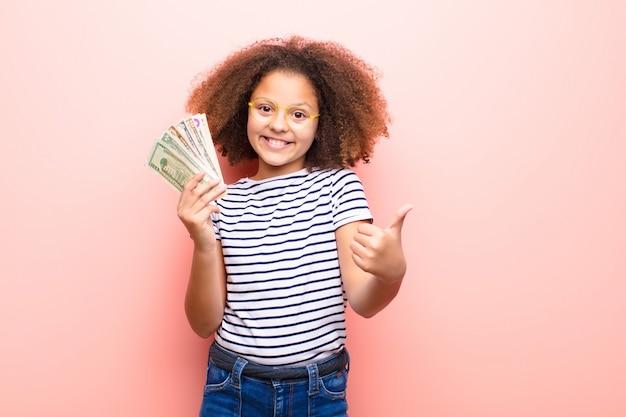 Bambina afroamericana contro la parete piana con le banconote del dollaro