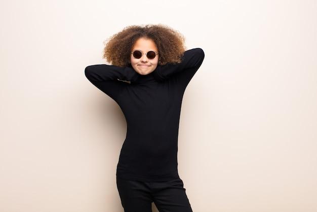 Bambina afroamericana contro la parete piana. concetto interessante