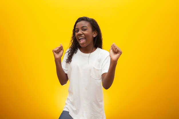 Bambina afroamericana felice a giallo, copyspace. ritratto di bel bambino che si diverte