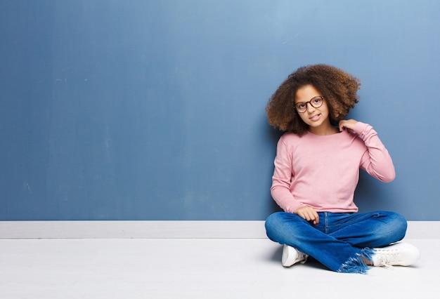 Bambina afroamericana sentirsi stressata, ansiosa, stanca e frustrata, tirando il collo della camicia, sembrando frustrata dal problema seduto sul pavimento