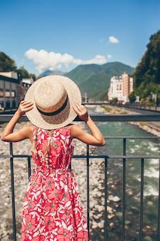 Bambina al cappello sull'argine di un fiume di montagna in una città europea.
