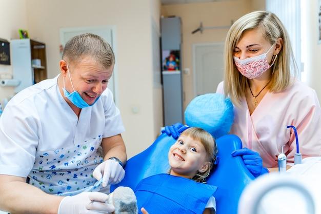 Bambina al gabinetto del dentista. squadra del dentista che lavora.