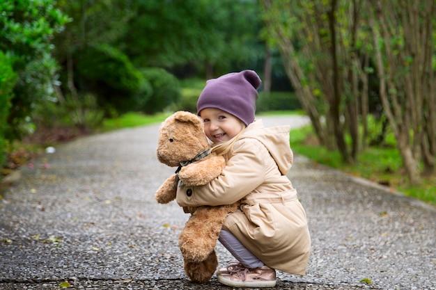 Bambina alla moda che abbraccia il suo orsacchiotto di peluche nel parco di autunno