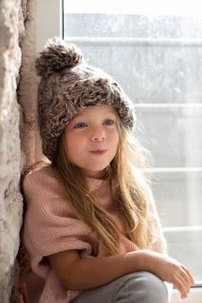 Bambina alla moda che posa con il cappello di inverno