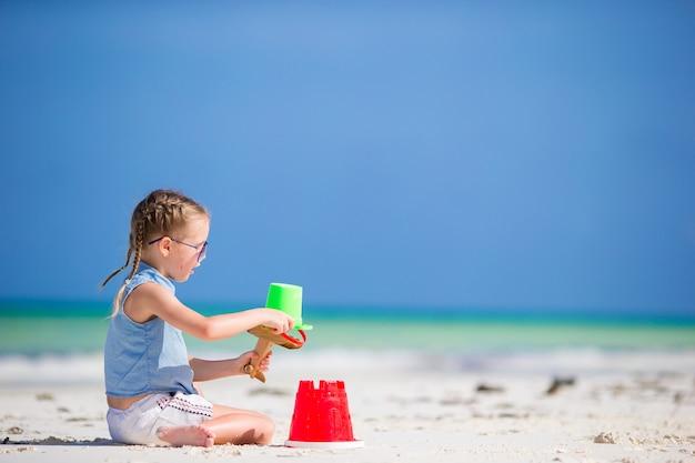 Bambina alla spiaggia bianca tropicale che fa il castello della sabbia