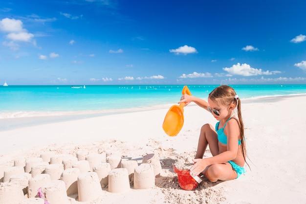 Bambina alla spiaggia bianca tropicale che fa il castello di sabbia