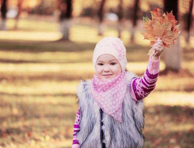 Bambina alle foglie della tenuta di autunno