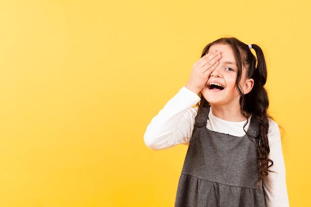 Bambina allegra che copre l'occhio con la mano