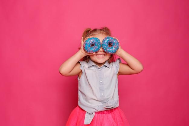 Bambina allegra con una ciambella su uno sfondo rosa. il bambino si dedica al cibo. divertimento con le ciambelle