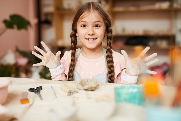 Bambina allegra in classe di ceramica