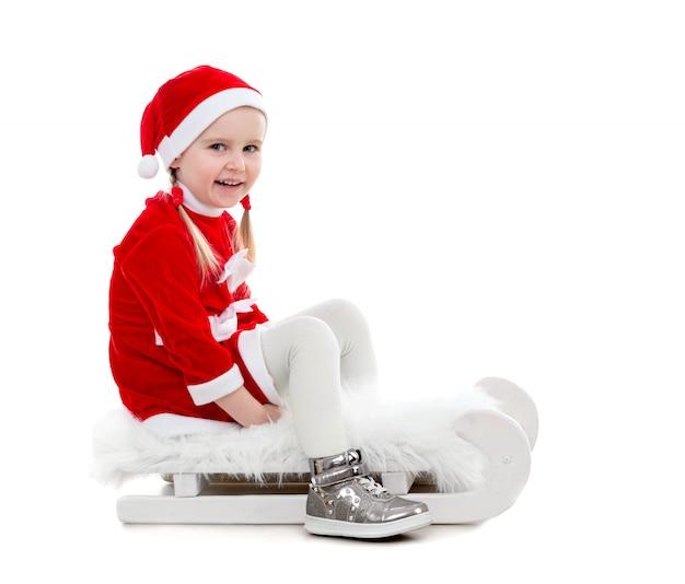 Bambina allegra in vestito di santa che si siede su una slitta