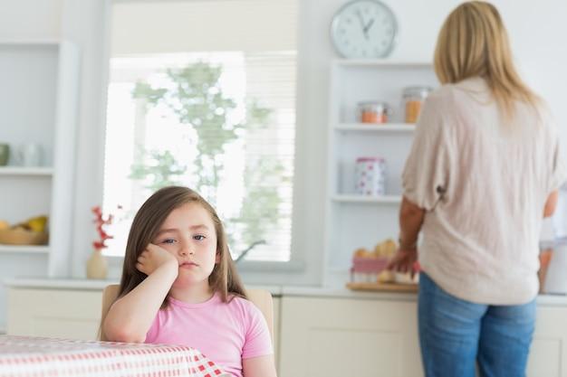 Bambina annoiata in cucina