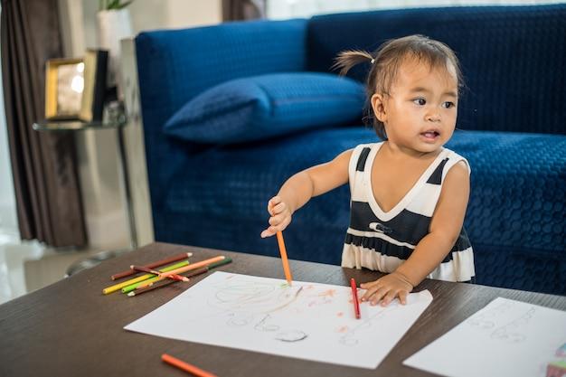 Bambina asia disegno familiare su un grande foglio di carta bianca