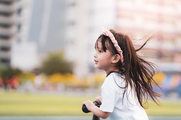 Bambina asiatica adorabile attiva che osserva in avanti con determinazione mentre sta giocando il motorino