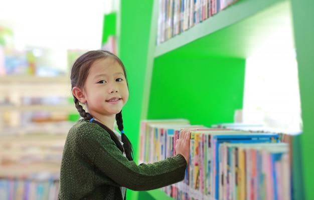 Bambina asiatica adorabile che cerca libro sullo scaffale per libri alla biblioteca