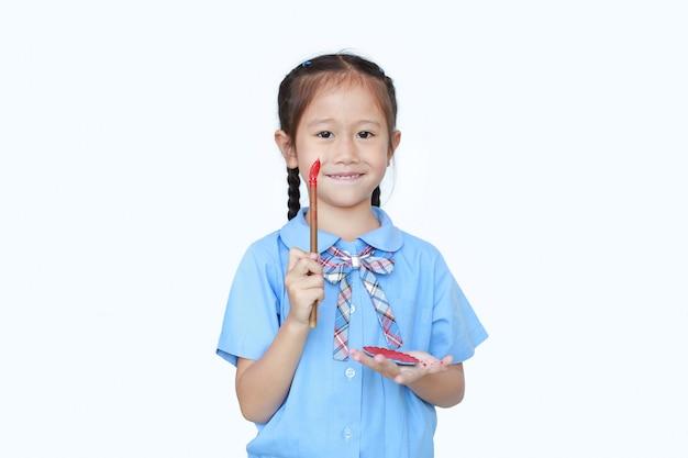 Bambina asiatica allegra in uniforme scolastica che tiene pennello e tavolozza immersi rossi