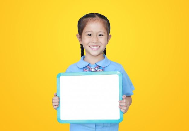 Bambina asiatica allegra in uniforme scolastico che giudica lavagna bianca in bianco isolata. concetto di studente e istruzione.