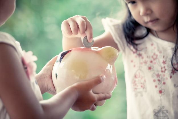 Bambina asiatica bambina mettendo moneta in piggy bank