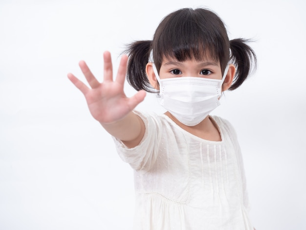 Bambina asiatica carina 4 anni che indossa una maschera igienica per proteggere il virus corona covid-19 influenza fredda o inquinamento sul muro bianco
