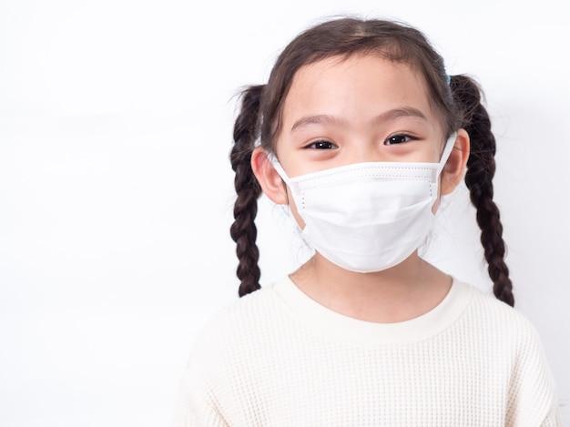 Bambina asiatica carina 6 anni che indossa una maschera igienica per proteggere il virus corona covid-19 influenza fredda o inquinamento sul muro bianco