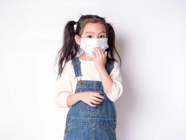 Bambina asiatica carina 6 anni che indossa una maschera protettiva per diffondere la malattia